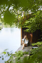 Relaxed woman sitting on wooden jetty at a remote lake - PNEF01034