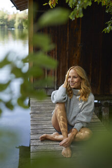 Relaxed woman sitting on wooden jetty at a remote lake - PNEF01046