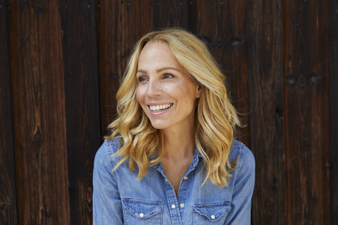 Happy blond woman in front of wooden wall - PNEF01049