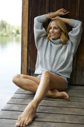 Smiling relaxed woman sitting on wooden jetty at a lake - PNEF01052