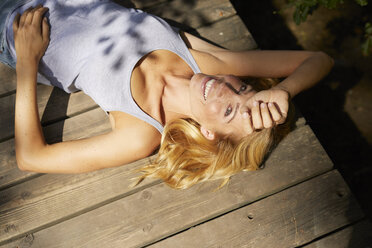 Happy blond woman lying on wooden jetty in sunshine - PNEF01055