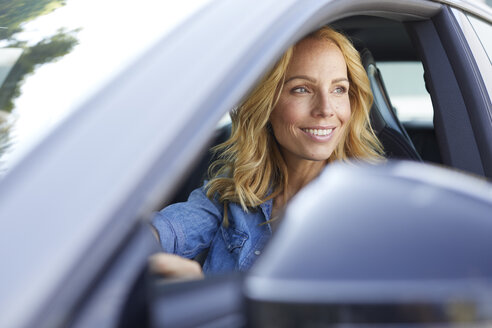 Smiling woman driving car looking out of window - PNEF01058