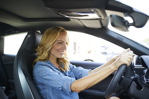 Smiling woman driving car - PNEF01061