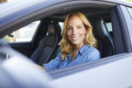 Portrait of smiling woman driving car looking out of window - PNEF01064