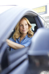Smiling woman driving car looking out of window - PNEF01067