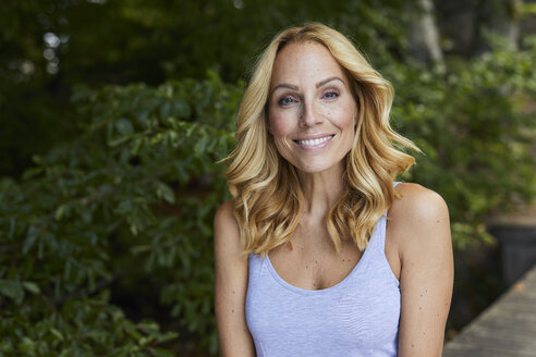 Portrait of smiling blond woman outdoors - PNEF01070