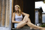 Smiling blond woman sitting on jety in front of wooden hut - PNEF01073