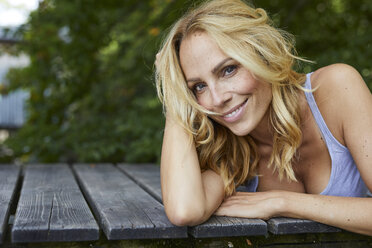Portrait of smiling blond woman lying on wooden jetty - PNEF01079