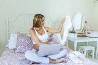Smiling pregnant woman with laptop sitting on the bed looking at baby clothes - KIJF02036