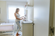Pregnant woman preparing the baby room - KIJF02048