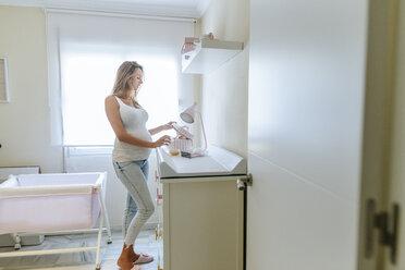 Pregnant woman preparing the baby room - KIJF02048