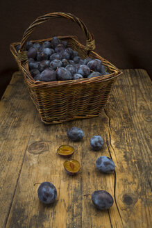 Wicker basket of organic plums, wooden table - LVF07463