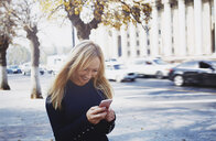 Smiling blond woman using smartphone in the city - AZF00096