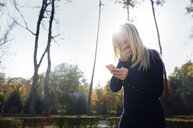 Laughing blond woman looking at her smartphone in autumnal park - AZF00105