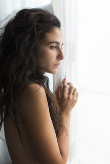 Young naked woman looking through window - JPTF00023