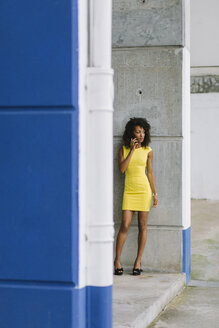 Fashionable businesswoman in yellow dress on the phone - FMGF00067