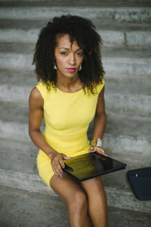 Portrait of fashionable businesswoman in yellow dress sitting on stairs with digital tablet - FMGF00070