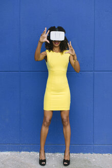 Woman in yellow dress using Virtual Reality Glasses against blue background - FMGF00073