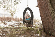 Cute girl playing in tire swing in snowy yard - FSIF03281