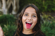 Close-up portrait of girl sticking out tongue at park - CAVF49120