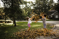 Playful siblings throwing dry leaves on each other at park during autumn - CAVF49126