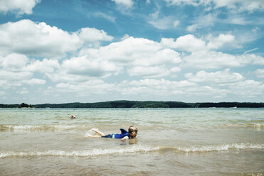 Boy wearing swimming goggles while lying in sea against cloudy sky - CAVF49141