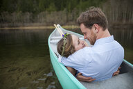 Young couple looking each other face to face while relaxing in canoe on lake - CAVF49150