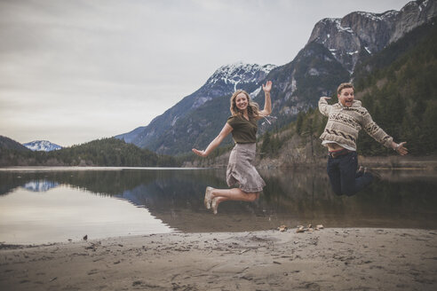 Full length portrait of playful young couple jumping on lakeshore at Silver Lake Provincial Park - CAVF49156