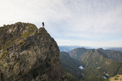 Mid distance view of hiker standing on cliff against sky - CAVF49165