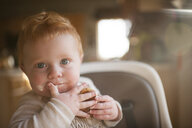 Portrait of cute baby boy eating food at home - CAVF49183