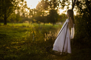 Side view of girl in dress swinging at park during sunset - CAVF49216