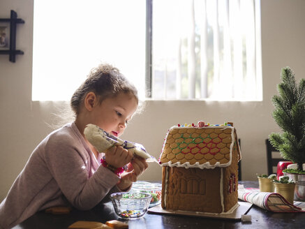 Side view of girl icing gingerbread house on table at home - CAVF49219