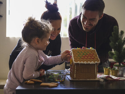 Happy parents looking at daughter decorating gingerbread house on table - CAVF49222