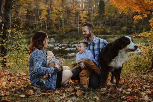 Parents enjoying with sons and dog on grassy field in forest during autumn - CAVF49225