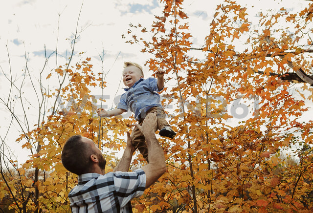 Low angle view of father throwing son while standing against sky in forest during autumn - CAVF49228
