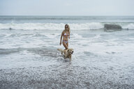Woman and Labrador Retriever walking on shore in sea at beach - CAVF49237