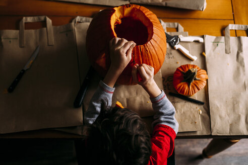 Overhead view of boy making jack o' lantern on table at home - CAVF49246