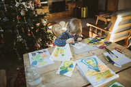 High angle view of girl painting on paper at home during Christmas - CAVF49249