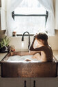 Shirtless boy taking bath while sitting in kitchen sink at home - CAVF49252