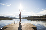 Full length of playful father throwing son in air against lake and sky during sunny day - CAVF49282