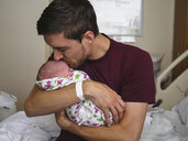 Father kissing newborn son while sitting on bed at hospital - CAVF49324