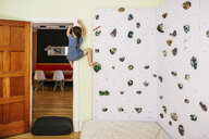 Full length of girl practicing on climbing wall in bedroom at home - CAVF49330