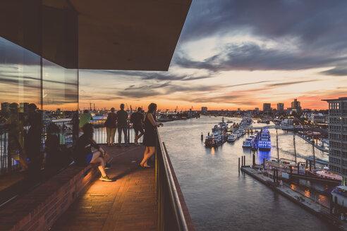 Germany, Hamburg, People on Plaza observation deck of Elbe Philharmonic Hall, view of Port of Hamburg at sunset - KEB00952