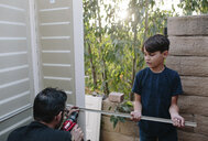 Son assisting father in drilling metal on door - CAVF49358