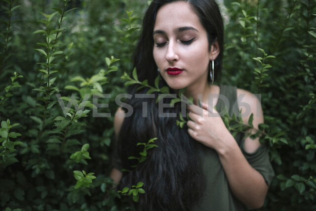 Close-up of teenage girl with eyes closed standing amidst plants at park - CAVF49373