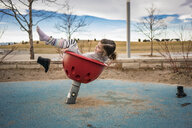 Side view of playful girl throwing shoes while playing on outdoor play equipment against cloudy sky at park - CAVF49379