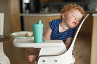 Close-up of cute baby boy with food and drink sleeping on high chair at home - CAVF49397