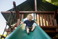Low angle portrait of happy baby boy screaming while sliding at yard - CAVF49400