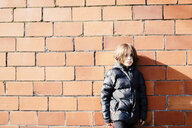 Portrait of boy wearing warm clothing while standing by brick wall - CAVF49403