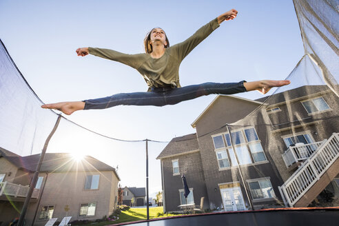 Low angle view of playful girl with legs apart and arms outstretched jumping on trampoline against houses - CAVF49412